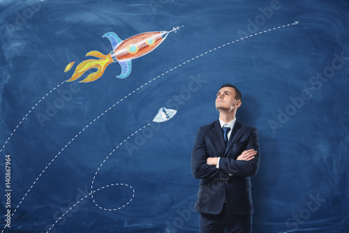 A businessman standing with his arms folded on the dark blue background, he is looking up at the pictures of the rocket and the UFO drawn on the wall.