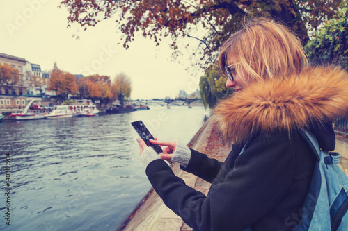 Cute girl using cellphone with Seine river in the background, Paris - France.
