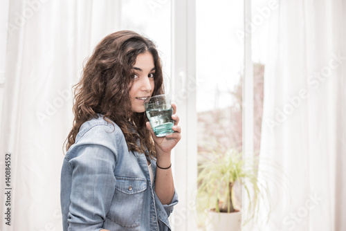 Poster Junge Frau zu Hause mit einem Glas Wasser