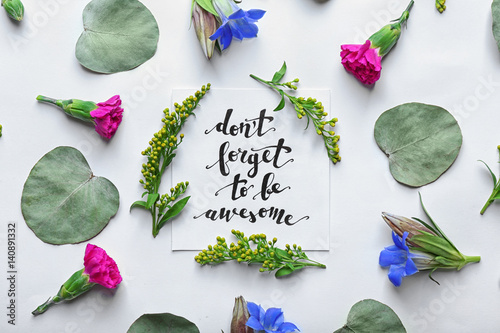 "Poster Inscription ""DON'T FORGET TO BE AWESOME"" written on paper with flowers and leave"