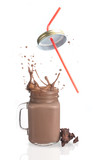 Milk chocolate splash with straw over white background
