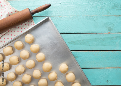 Dough and wooden rolling pin on blue wooden table