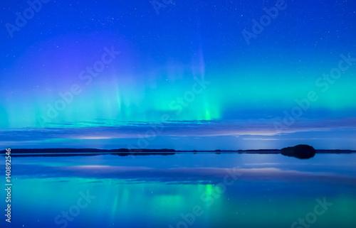 Northern lights dancing over calm lake (Aurora borealis)
