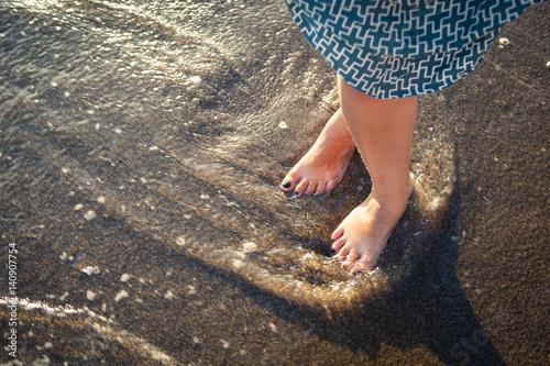 Beautiful bare female feet on the beach