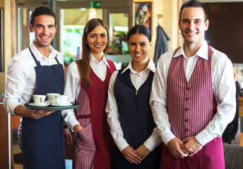 Portrait of cafe staff standing in bar.