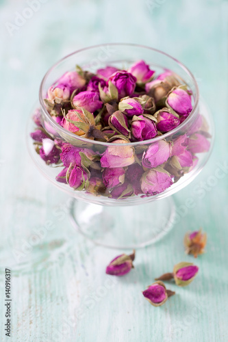 dried rose buds on turquoise wooden surface