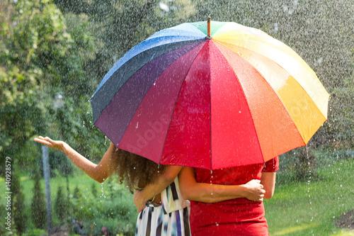 Couple under rainbow umbrella