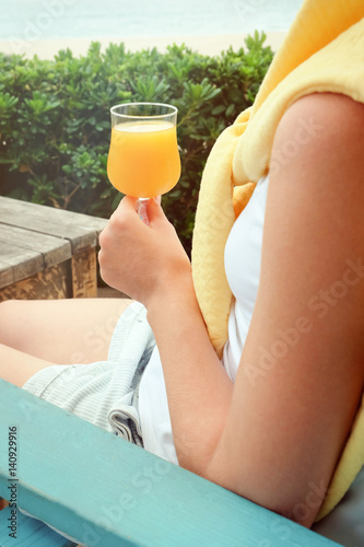 Closeup of woman holding glass of orange juice while sitting at cafe outdoors