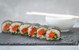 Healthy homemade sushi rolls with brown rice, fish and green vegetable rolls.