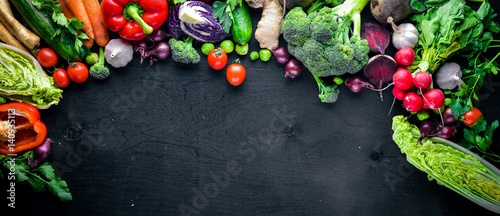 Fresh vegetables, chili, onion, garlic, herbs and spices.On a black wooden background. Free space for text . Top view