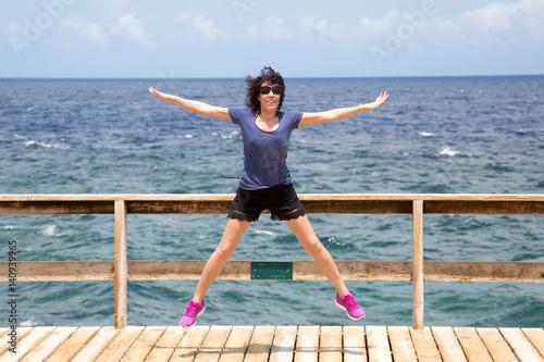 Luftsprung - Frau genießt karibisches Meer (Jump) Poster
