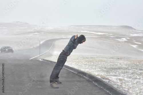 Woman tries to stand against winter storm, force of nature concept.