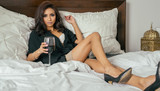 Beautiful elegant woman relaxing with a glass of wine in bed