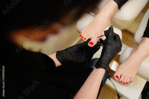 Aluminium Pedicure The nail wizard makes a pedicure to a girl. To paint nails in red color