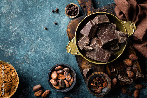 obraz lub plakat Dark chocolate pieces crushed and cocoa beans, culinary background, top view