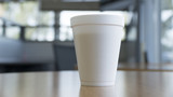 disposable coffee cup on table in a large bright room