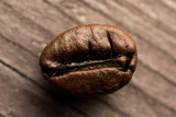 One coffee bean on wooden board, closeup