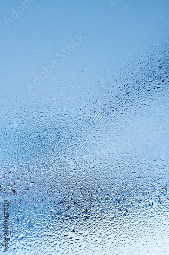 Naklejka na szybę Window glass with condensation, strong, high humidity in the room, large water droplets flow down the window, cold tone, natural water drops on window glass