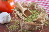 Dried oregano spice in burlap bag with wooden scoop on table. Concept image for cooking with oregano - 141015927