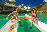 Beautiful girls in bikini relaxing on a canoe at the tropical resort - 141018150