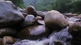 Big stones and large rocks on mountain river stream close up slider view. Fresh water splashes and flows through rocky cascades in wild nature of Sumatra, Indonesia - 141032348