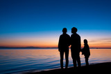 silhouette of three people standing on the beach in sunrise