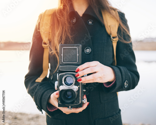 Midsection of hipster woman holding vintage twin-lens reflex camera