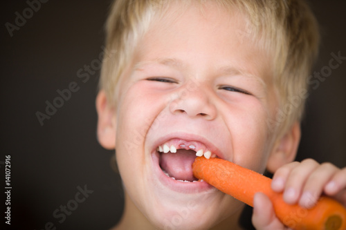 Poster Portrait of cute toothless kid boy eating carrot