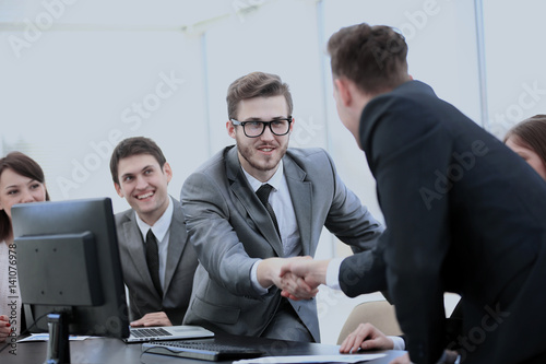 business partners near your Desk to shake hands as a sign of coo