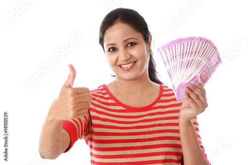 Poster Young woman holding 2000 rupee notes and making thumb up gesture