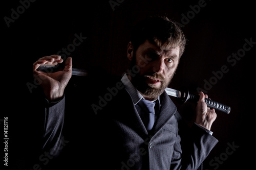 Poster stern angry businessman in a wool coat with sword in dark background