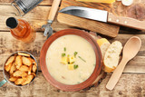 Delicious beer cheese soup with croutons and onion on table