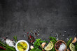 Selection of spices herbs and greens. Rosemary basil lemon olive oil pepper top view black background. - 141135541