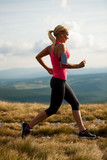 runner - woman runs cros country on a path in early autumn