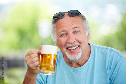 Mature man make cheers with beer Poster