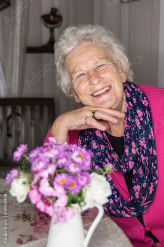 Poster Alte Dame fröhlich und schick sitzt am Tisch
