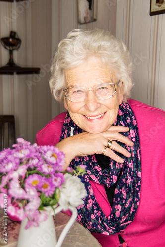 Poster Freundliche schicke Seniorin entspannt am Tisch