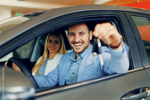 Poster Young couple holding the keys of a new car