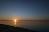 orange sunset over baltic sea with clear sky and clouds near sun, summertime photo