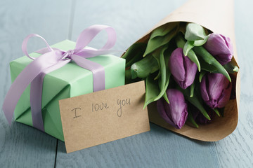 purple tulips in craft paper with gift box on blue wood background, with i love you greeting card