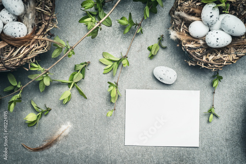 Easter eggs nest with bird feathers and blank white paper card, top view