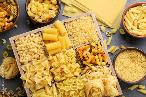 Different kinds of pasta on grey wooden table Poster