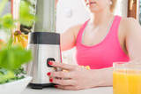 Athletic young woman prepares smoothie with fresh fruits