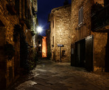Night view of beautiful Italian medieval Pienza city with lanterns. Travel outdoor Tuscany background.