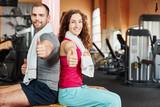 Paar im Fitnesscenter mit Daumen hoch