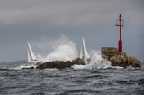 Two sailing boat in stormy weather close dangerous rock with red lighthouse