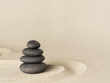 Balance and harmony, zen stone garden background. Dark black stones on fine sand standing for concentration and relaxation..
