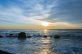 Beautiful sunrise on a sea shore with big stones