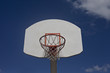 Cloudy blue sky frames old orange and white basketball goal.