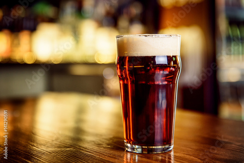 A glass of dark beer on counter Poster